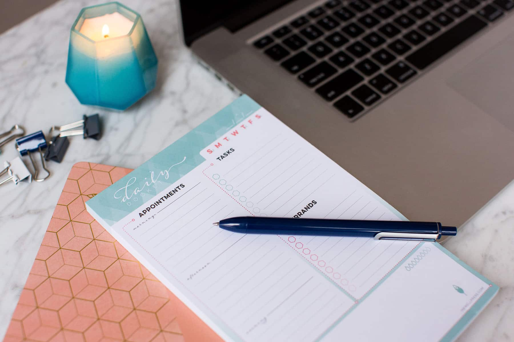 A pen rests atop an Inkwell Press Planner laying next to a macbook pro and a candle. Photographed by Rebecca Marie Art