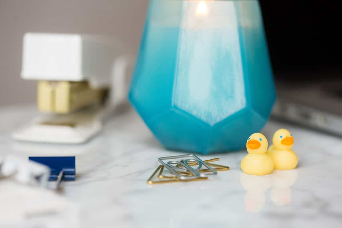 white stapler, blue candle, and mini rubber ducks sit on top of a desk with binder clips and paper clips