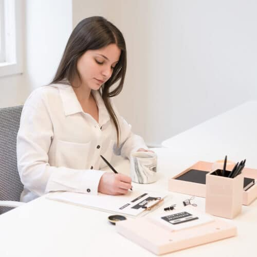a woman sits at a desk with a pen in hand as she works on her marketing plan
