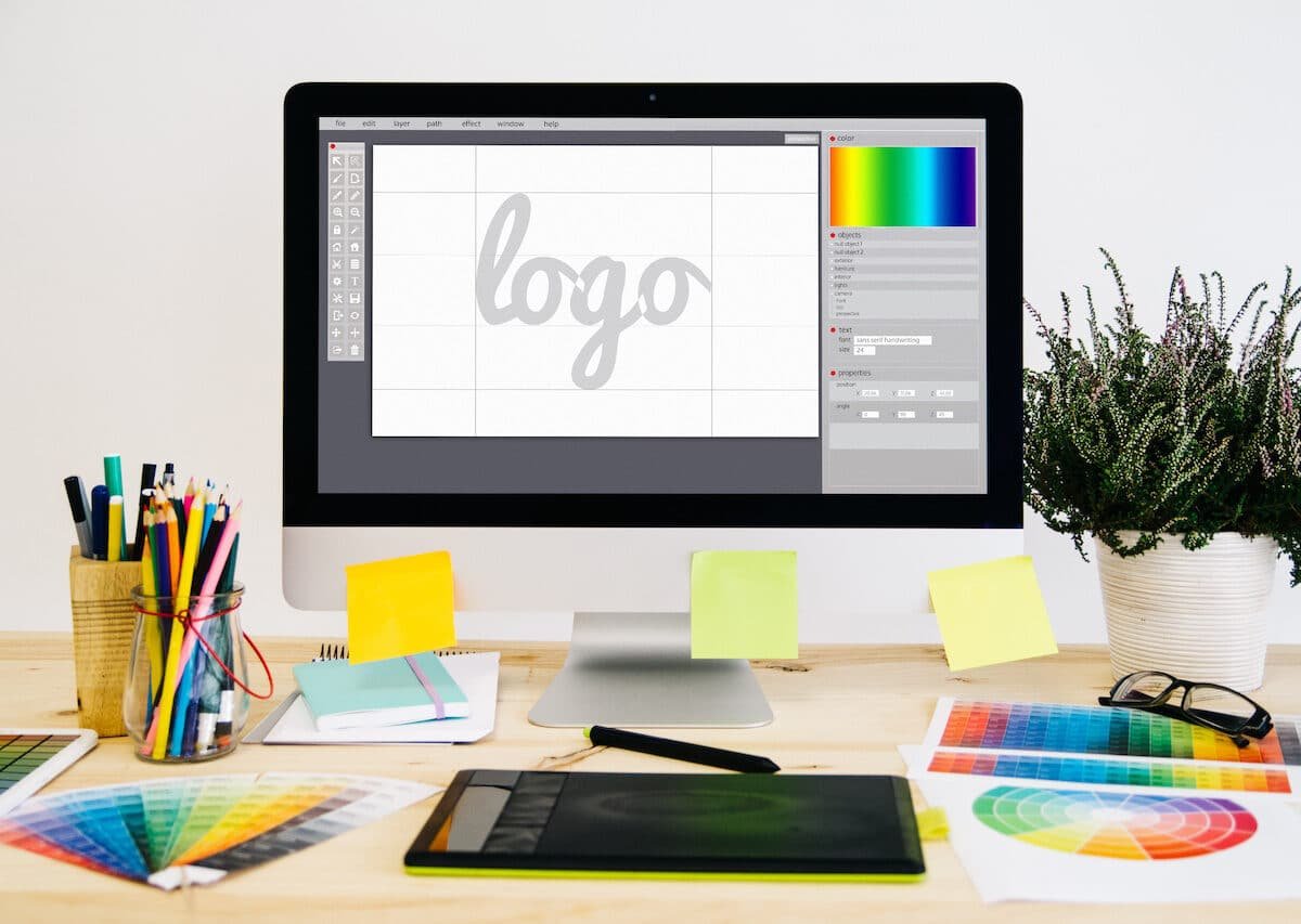 Stationery desktop with design stuff, a computer, and a graphic tablet showing logo design.