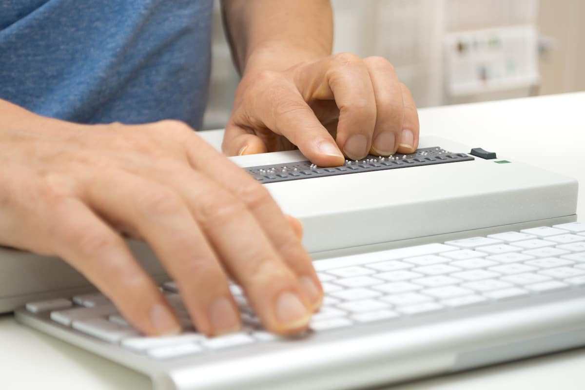 Visually impaired working on computer with assistive technology; braille display and keyboard.
