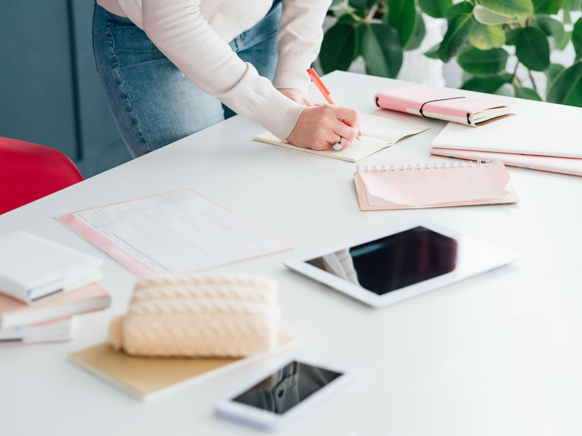 Social network business. Internet marketing. SMM woman at workplace making notes in schedule. Tablet and smartphone.