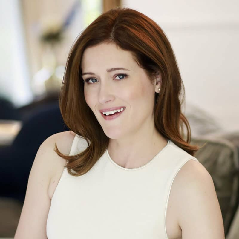 Portrait of Jenn Whinnem, a copywriter. She has dark auburn hair and is wearing a professional, white sleevless top. She has blue eyes and is looking at the camera, smiling slightly.