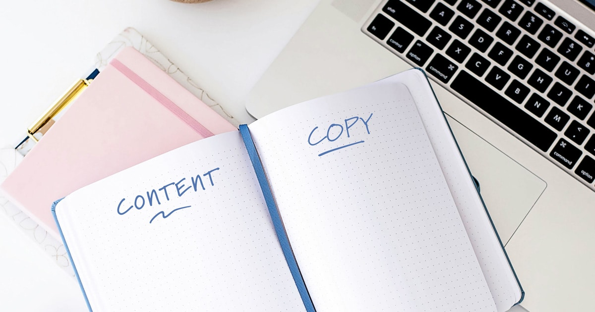 "An open notebook sitting on top of a laptop keyboard. On one page of the notebook, ""content"" is written and ""copy"" is written on the other page."