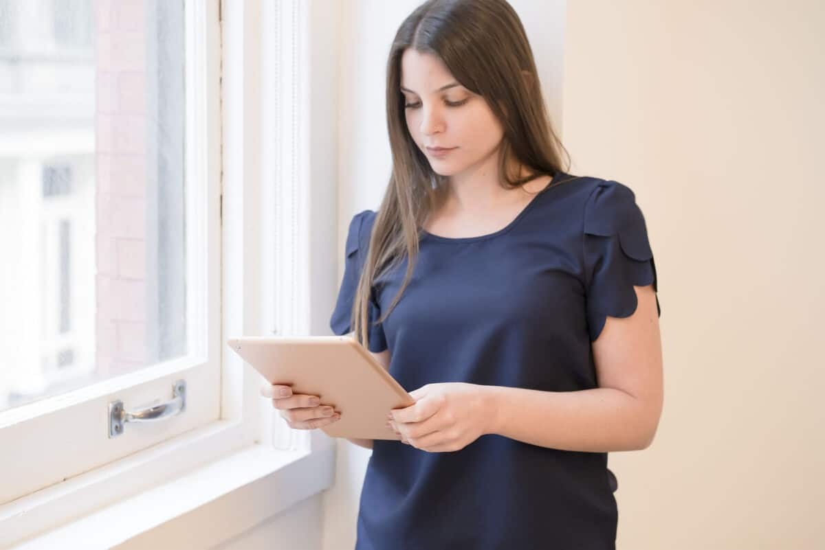 A woman standing, holding an iPad. She is using the iPad to search for a branding and design agency to work with.