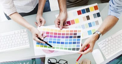 A team stand around a table viewing a multicolored piece of paper as they discuss why invest in branding?