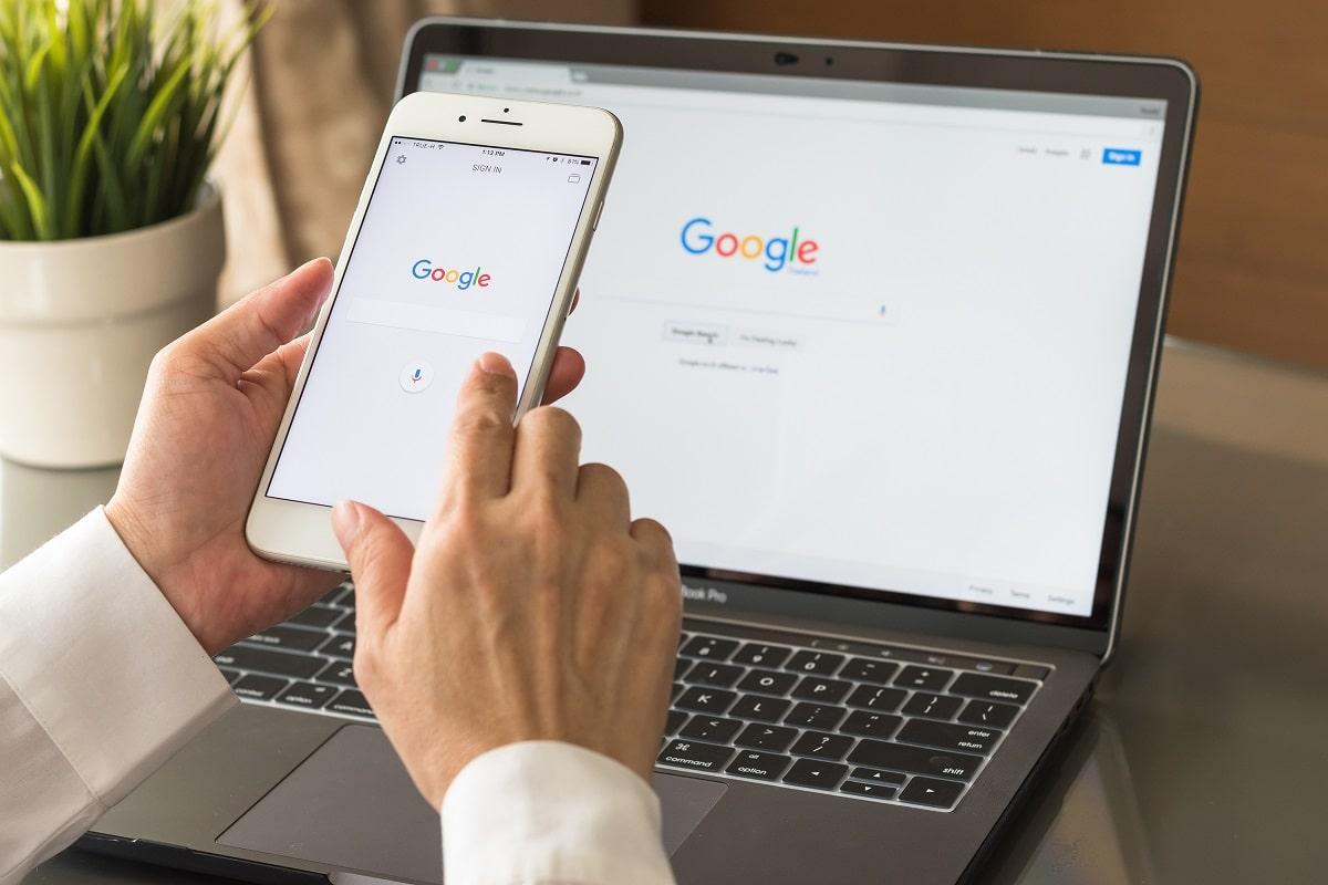 Google search engine sign up page on mobile app touchscreen on iphone in business person's hand and on computer screen display. The person is ready to use G Suite