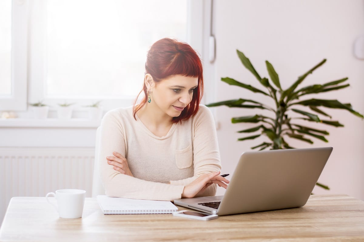 Young beautiful woman with red hair working in the office on writing blog headlines