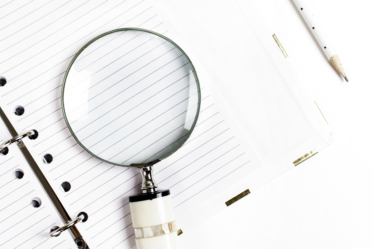 A magnifying glass on top of a lined notebook next to a pencil.