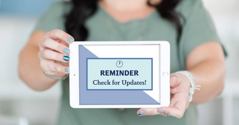 "A woman holding an iPad with ""Reminder: Check for Updates!"" on the tablet screen."