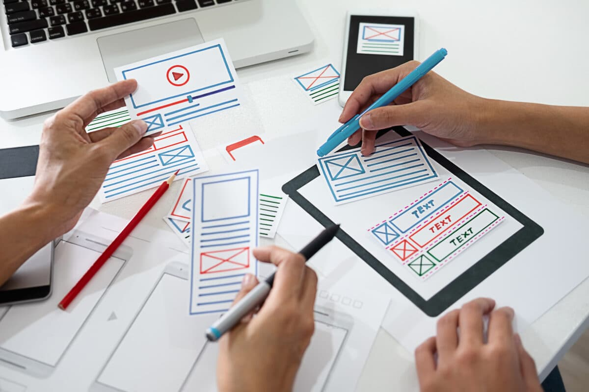 A graphic designer using paper cut outs to plan a website page layout.