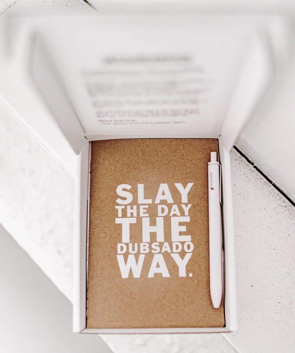 """A notebook and pen in an open box. Text on the notebook cover states """"Slay the day the Dubsado way"""""""