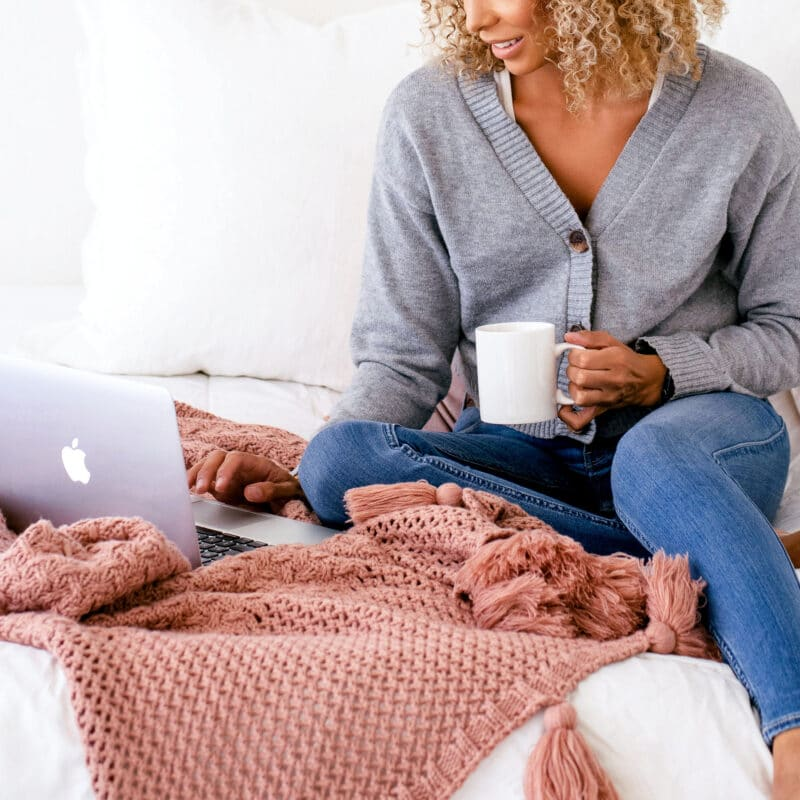 Woman holding a cup of coffee and working on her laptop to choose the best sidebar widgets for her website's blog
