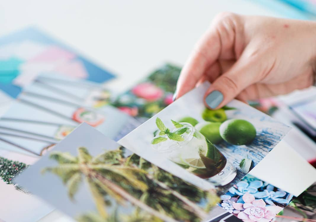 Multiple stock photos with similar color schemes from the same photo series on a table