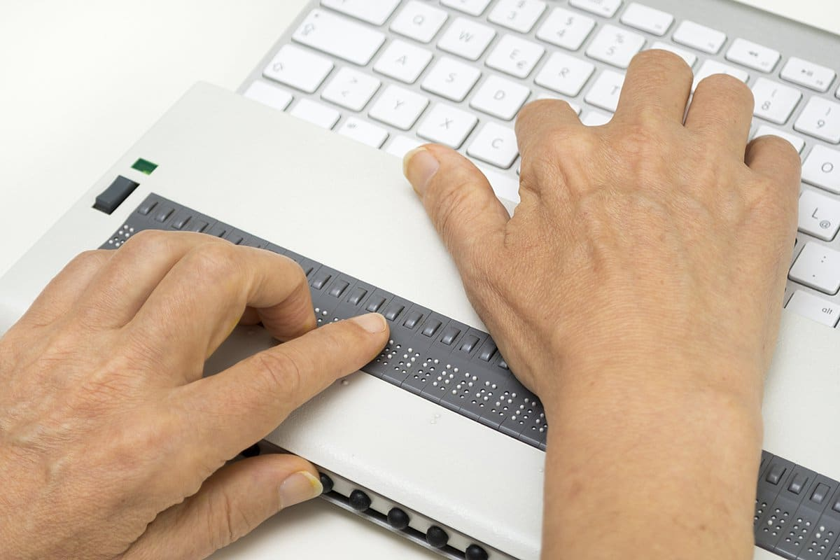 Visually impaired working on computer with assistive technology; refreshable braille display.
