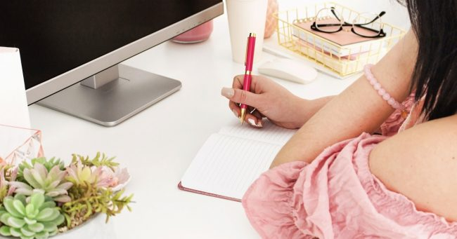 Woman sitting in front of her laptop writing in a notebook